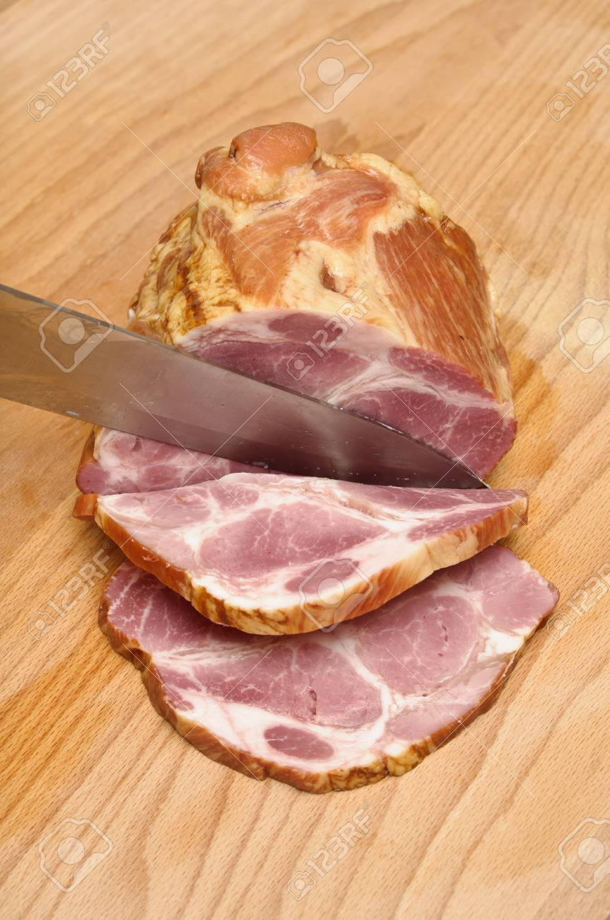Frontal view of pork loin slicing on a wooden board Stock Photo - 10801230