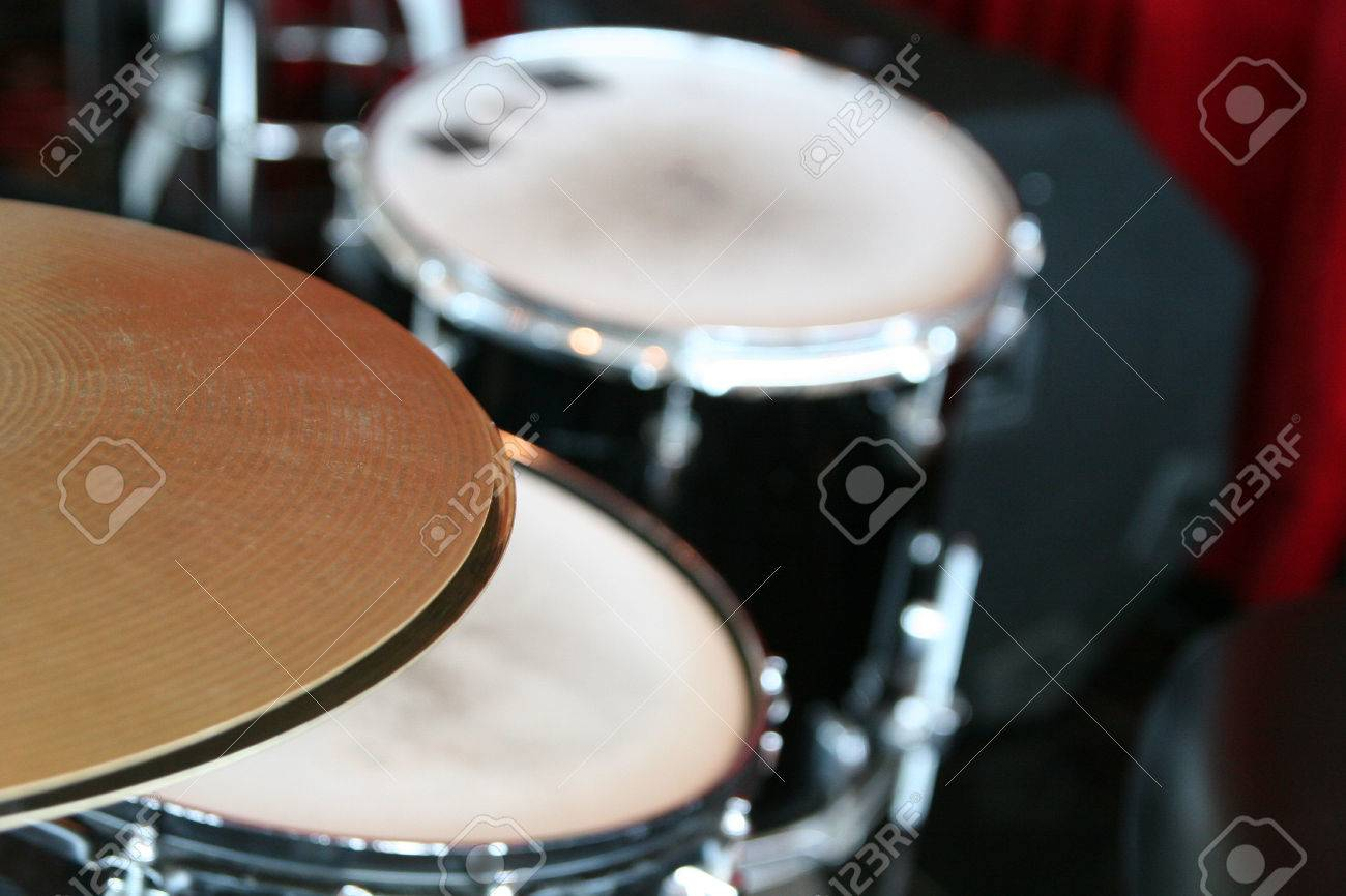 Close Up Of Cymbals With A Drum Set In The Background Stock Photo