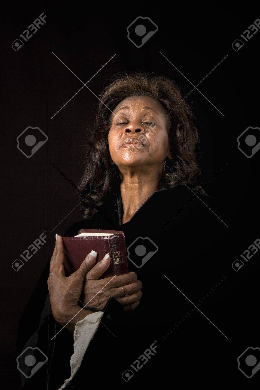A black woman holding a bible and closing her eyes in prayer