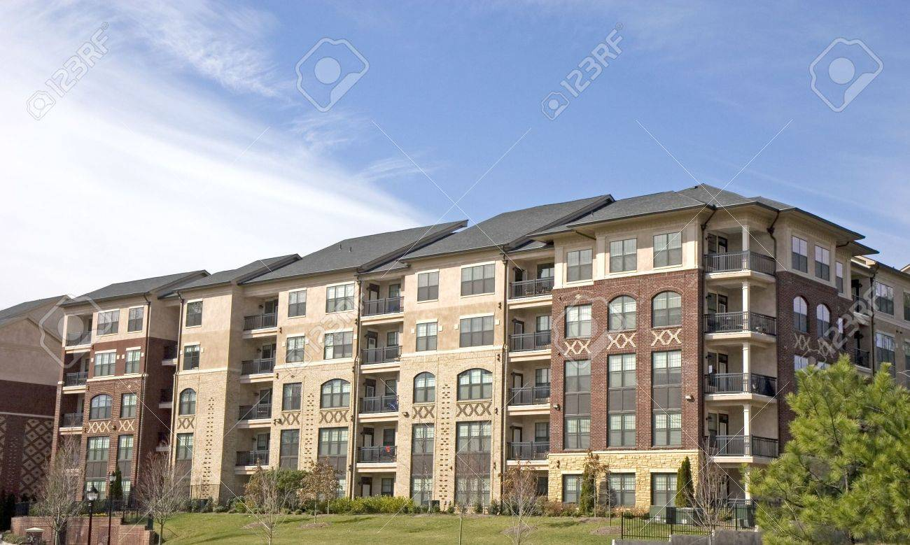 A modern brick apartment complex against a blue sky with clouds Stock Photo - 2819882