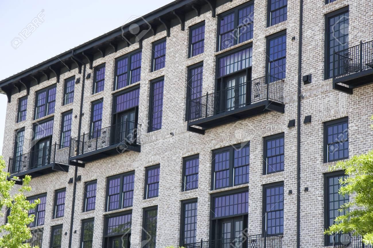 A Brick Loft Apartment Building With Colorful Purple Windows Stock