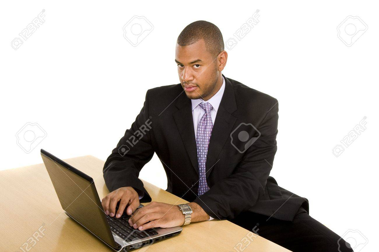 A Nice Looking Black Man In A Suit Sitting At A Desk Working