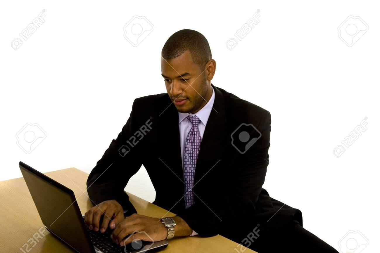 Un homme noir dans un joli tailleur assis à un bureau de taper sur
