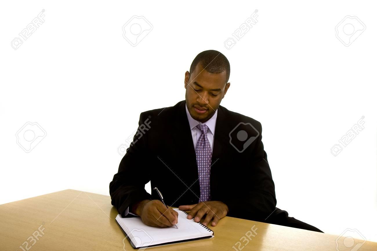 548366ab84cfc3 Banque d images - Un homme noir dans un beau costume à un bureau de travail  écrit dans un cahier