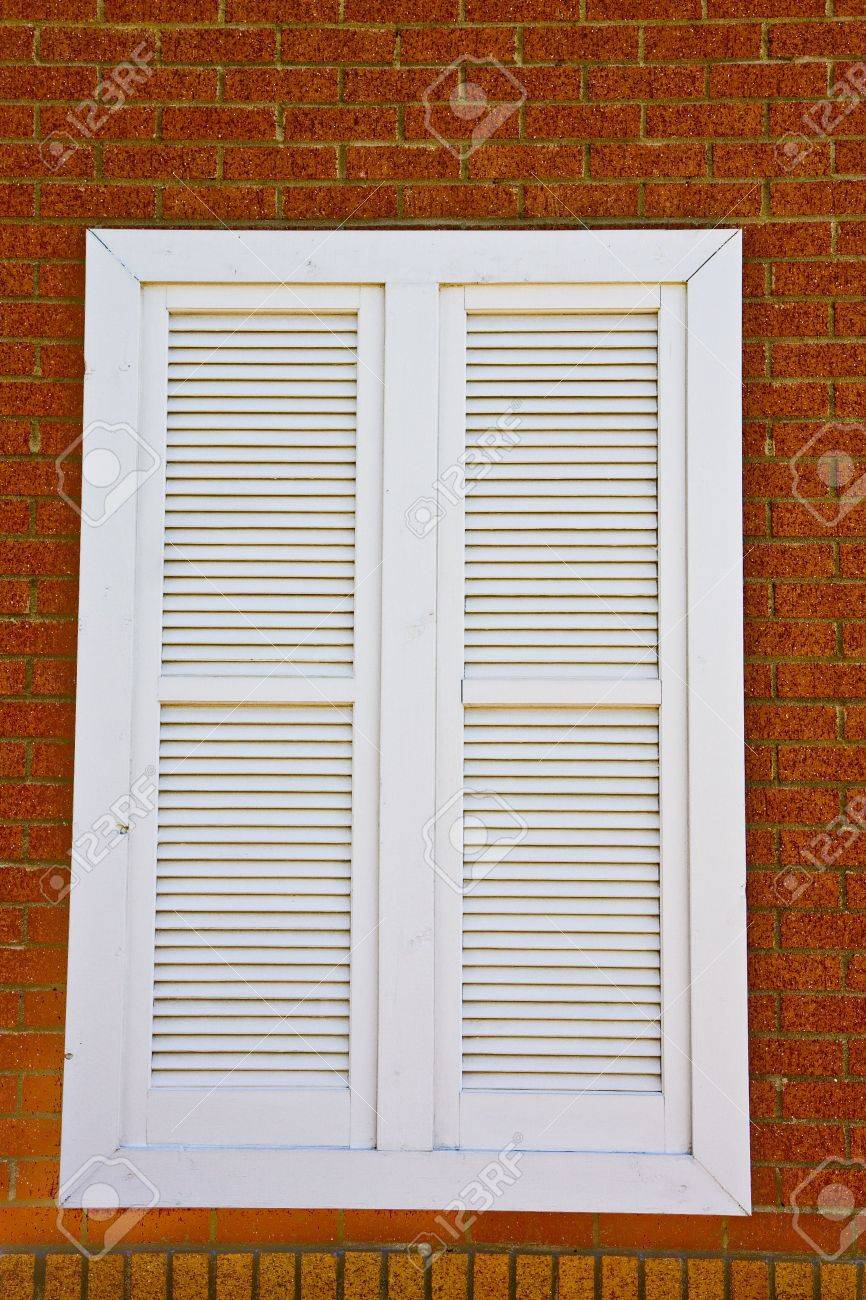 WhiteLouvered window on a red brick wall Stock Photo - 4514301