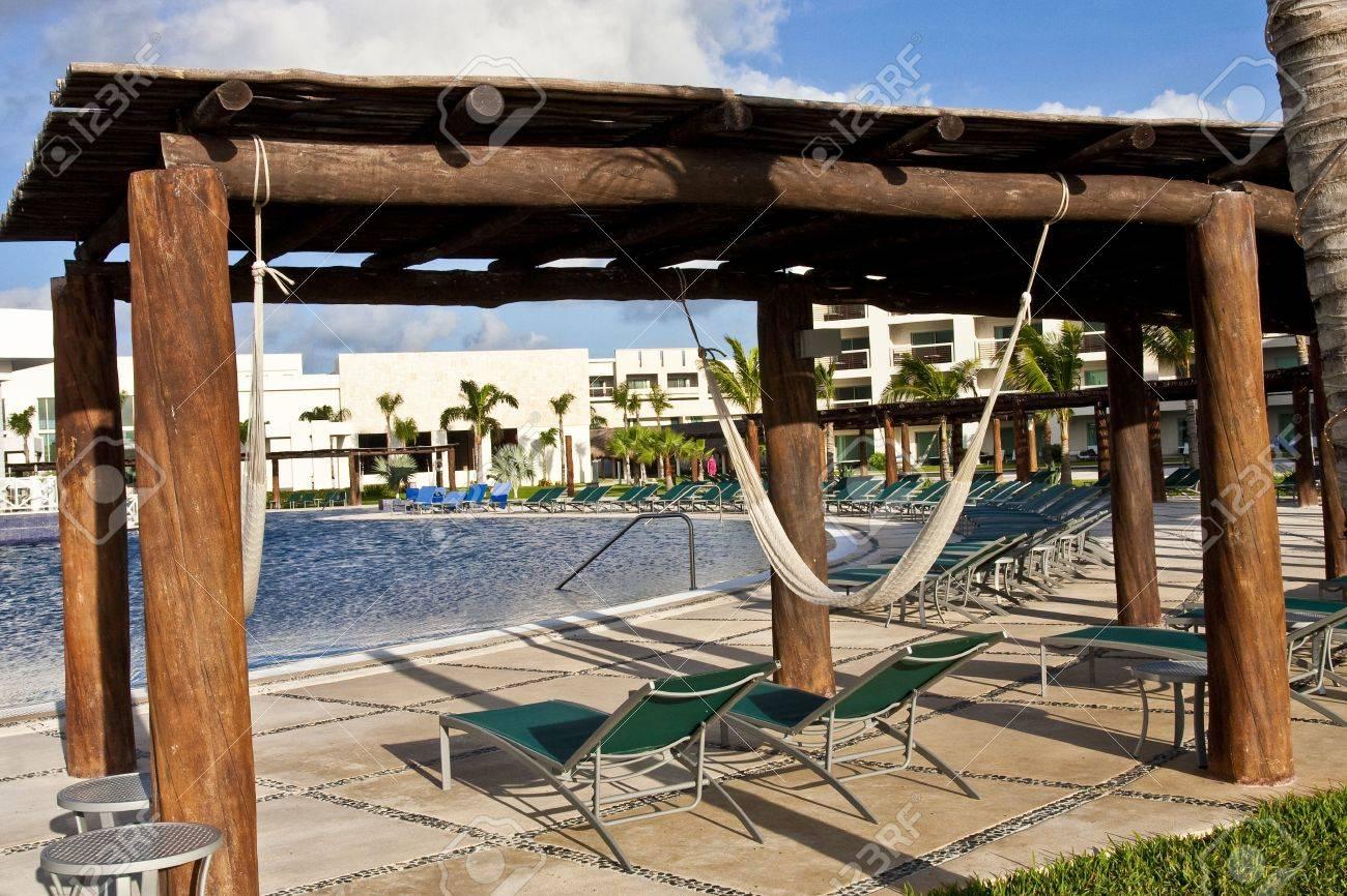 Hammocks hanging from bamboo shelter at a resort swimming pool