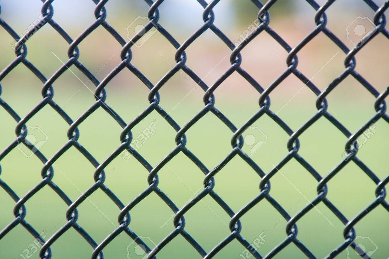 A black chain link fence with an out of focus green background Stock Photo - 9133594