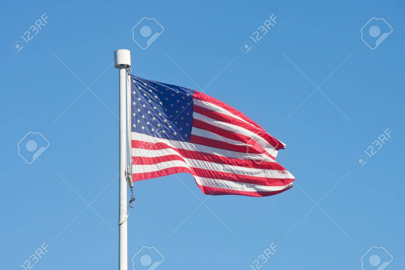 An American flag blowing in the wind on a flagpole in a clear blue sky Stock Photo - 9668727