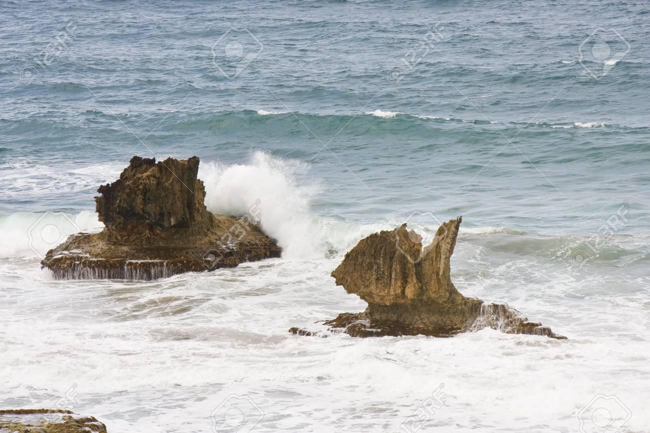 Ocean splashing against volcanic rocks lying in the surf Stock Photo - 11056079
