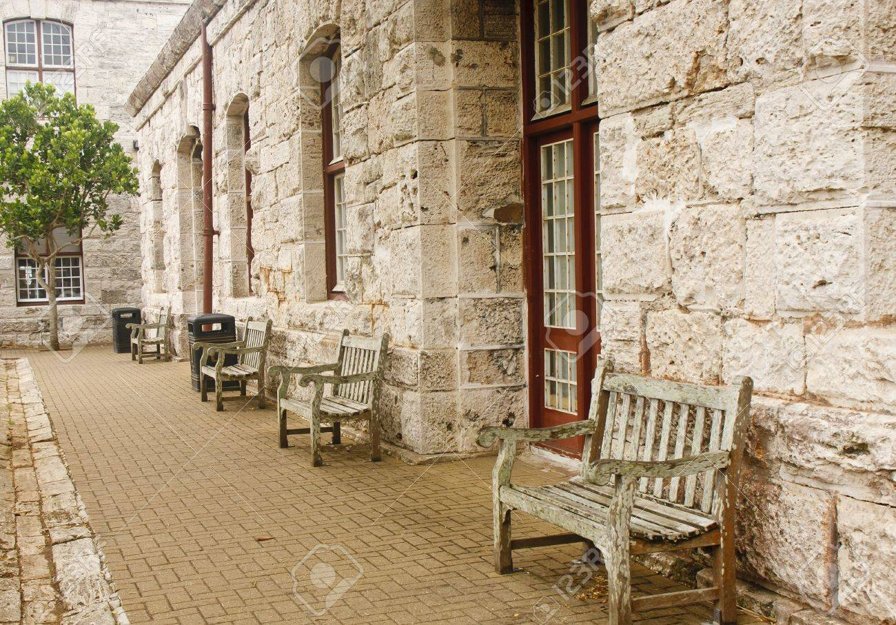 Outstanding An Old Stone Block Wall With Old Wooden Benches On Sidewalk Evergreenethics Interior Chair Design Evergreenethicsorg