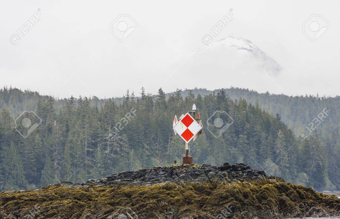 A red and white navigation marker on a green island in Alaska with snowy mountain behind fir trees Stock Photo - 16484366