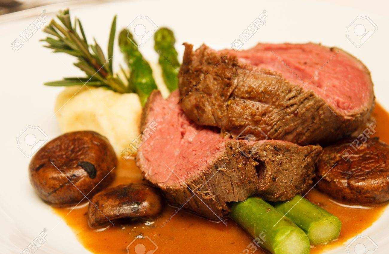 Rare Prime Rib Beef On A Plate With Mushrooms Gravy Asparagus Potatoes And