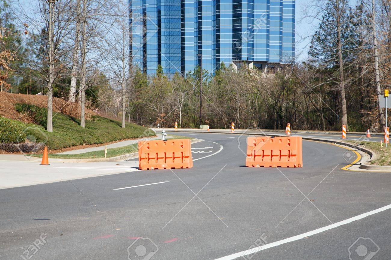 Orange traffic barriers in road in front of blue glass office