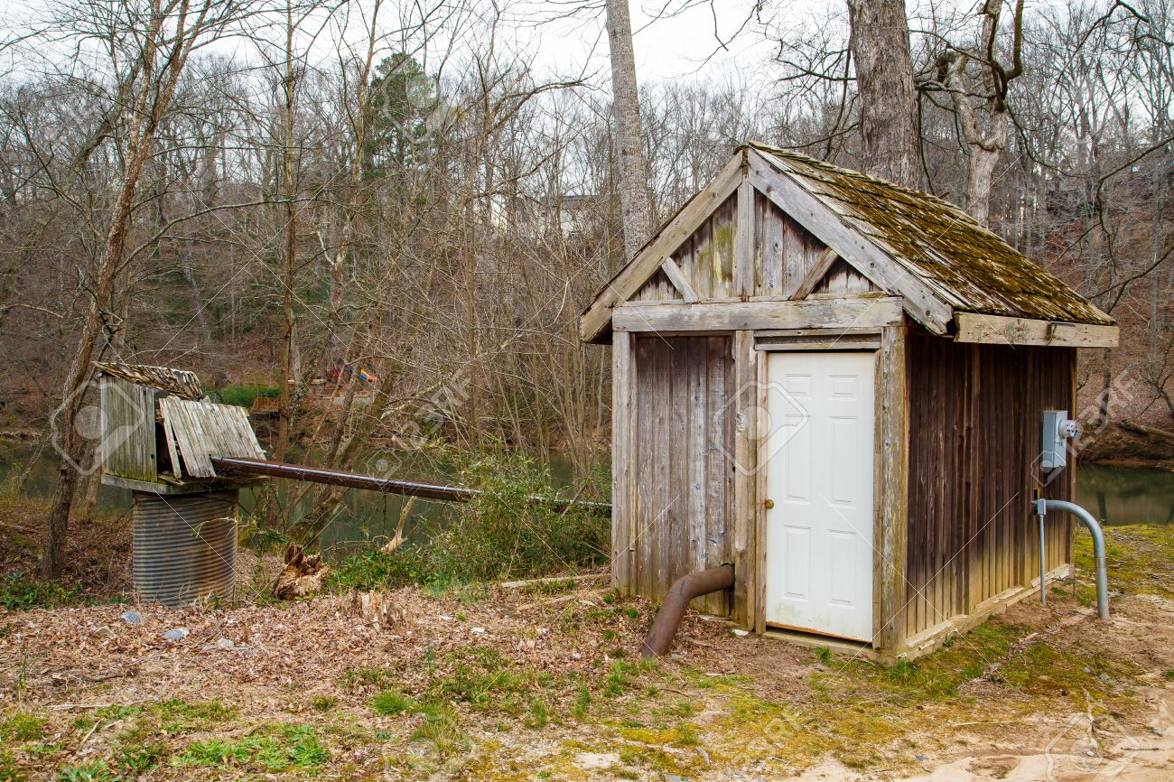 an old wood shed or pump house near a winter river stock photo
