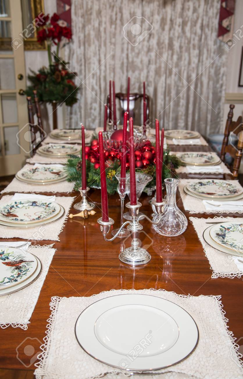 A formal dining room table set for dinner and decorated for Christmas