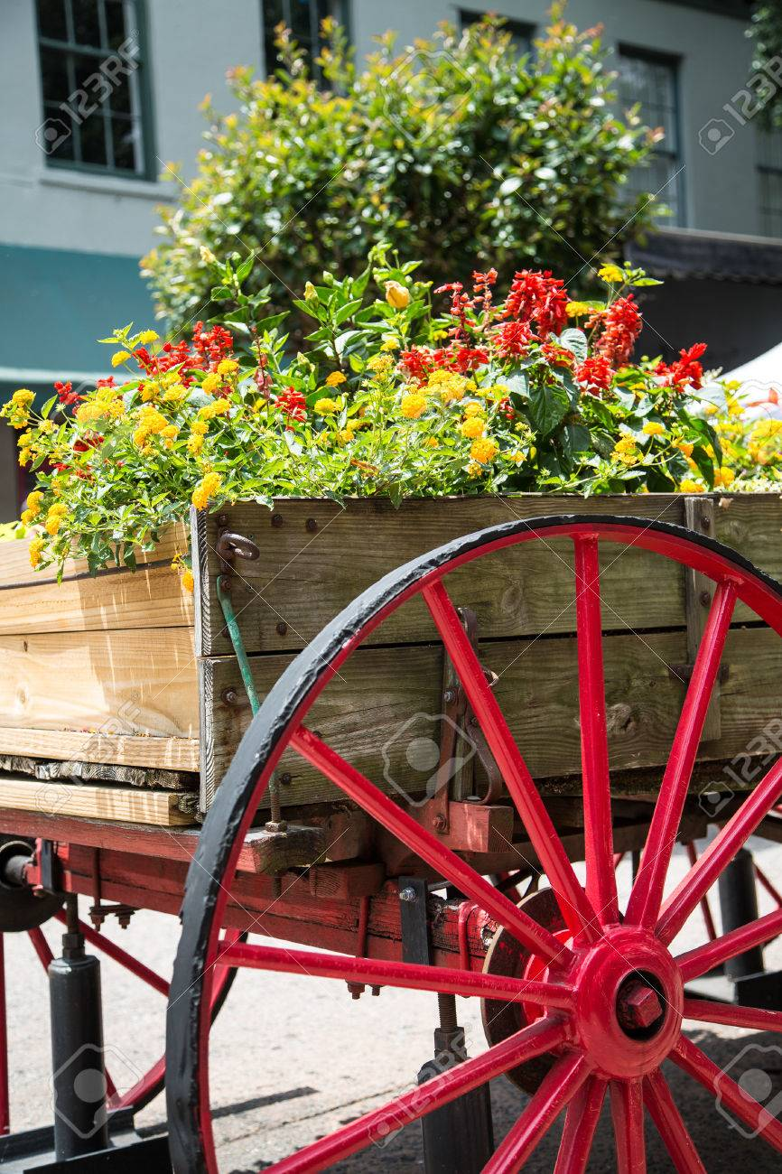An Old Wood Cart With Large Red Wagon Wheel Used As A Garden Stock