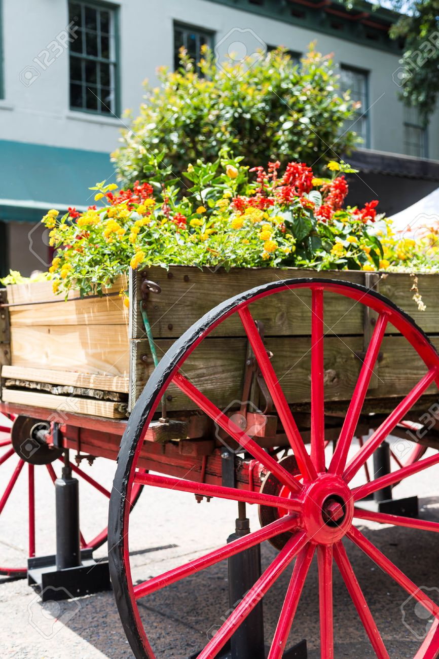 An Old Wood Cart With Large Red Wagon Wheel Used As A Garden Planter Stock  Photo