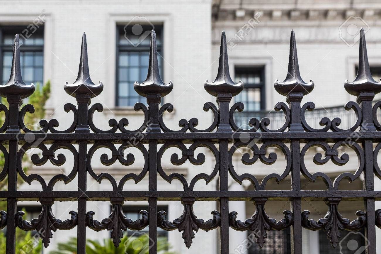 Ornamental wrought iron gates - Old Ornamental Wrought Iron Fence With Spiked Tops In Front Of Stone Building Stock Photo