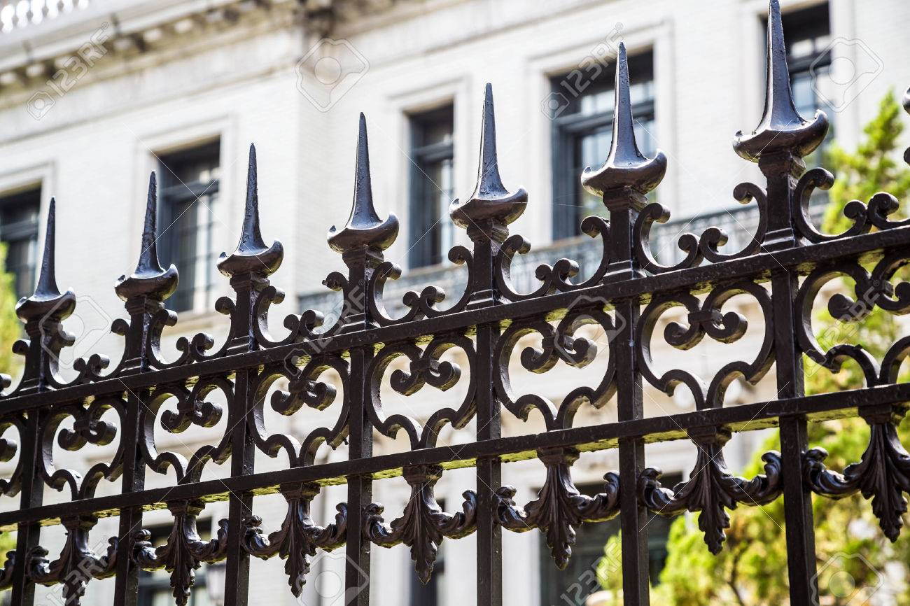 Old Ornamental Wrought Iron Fence With Spiked Tops In Front Of