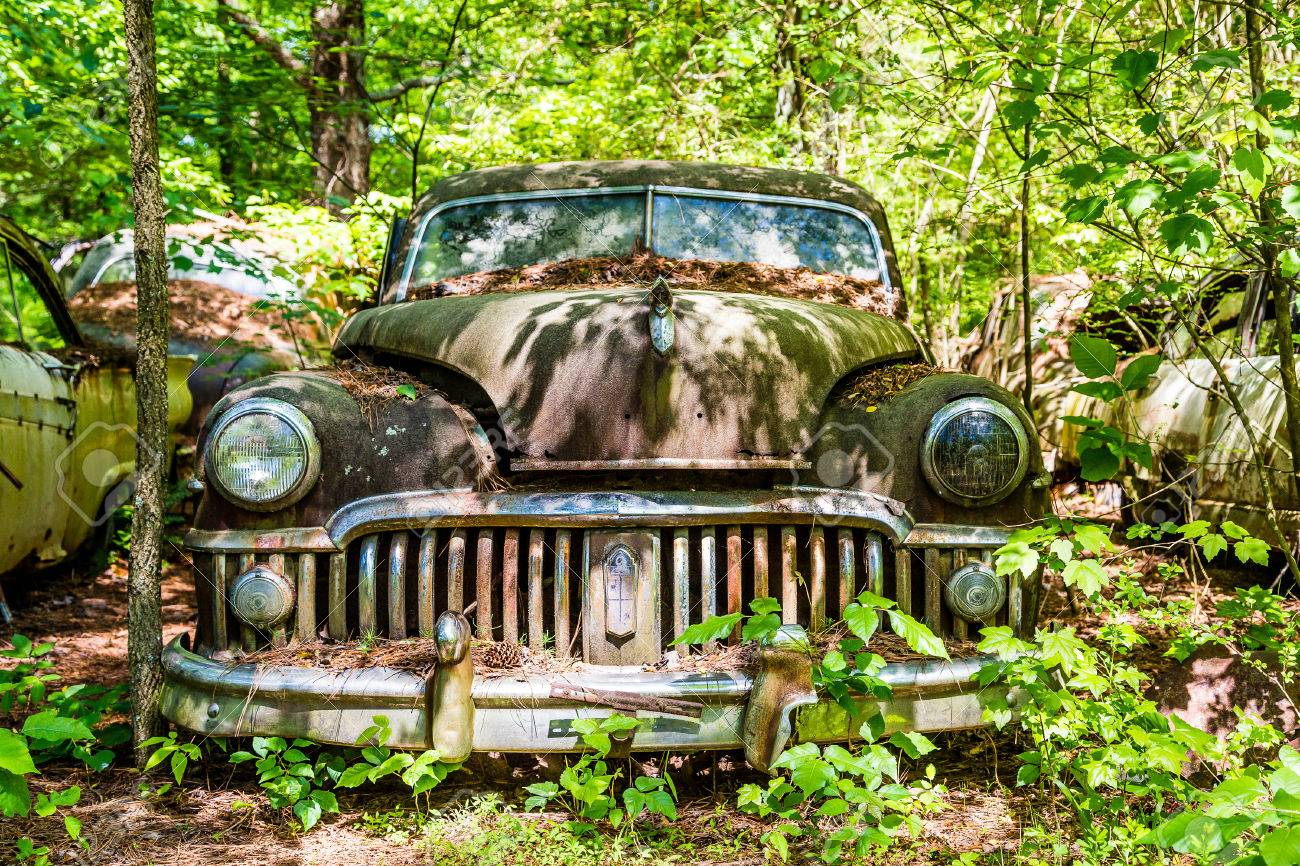 An Old Rusty Car Abandoned In The Woods Stock Photo Picture And