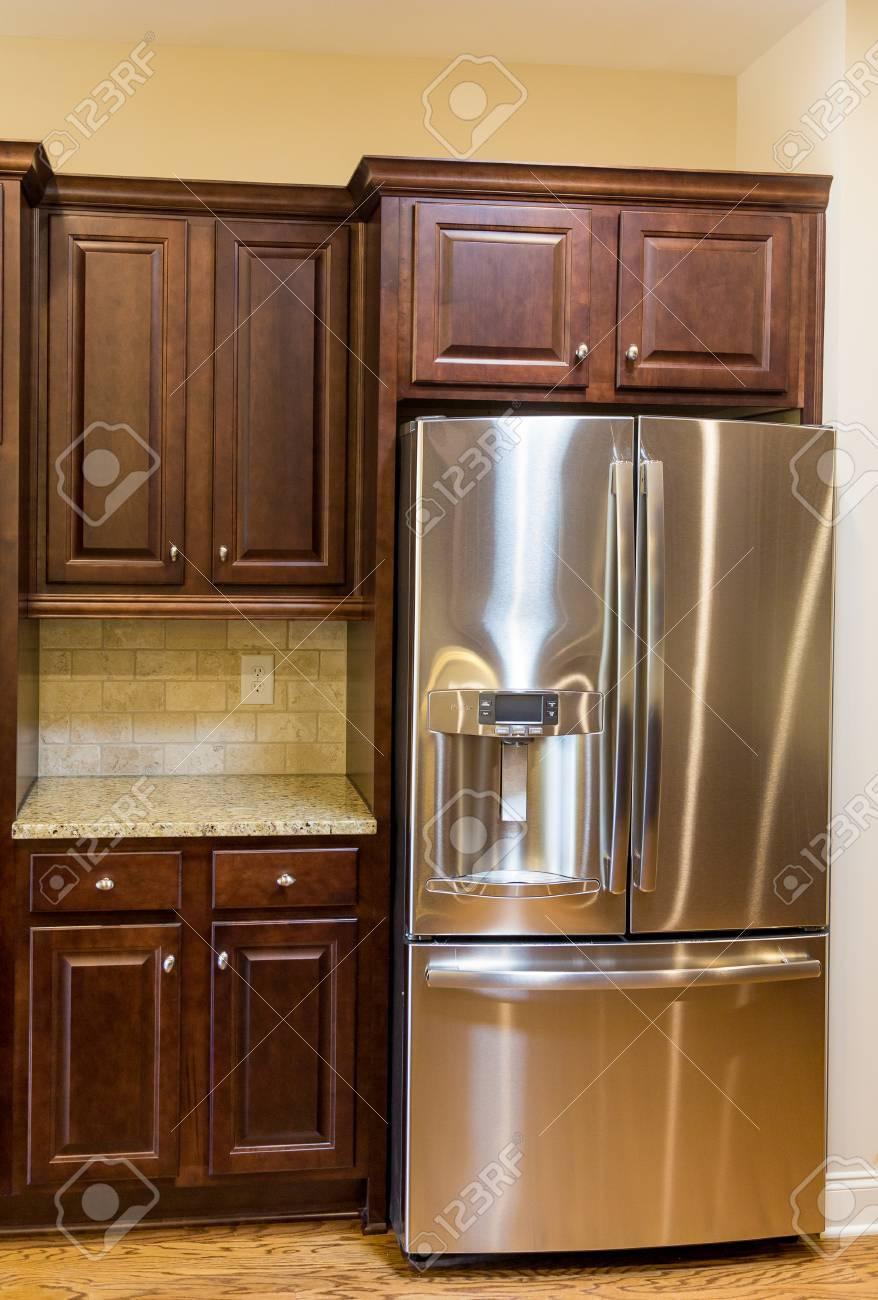 Electrodomésticos de acero inoxidable, encimeras de granito y muebles de  madera oscura en una nueva cocina