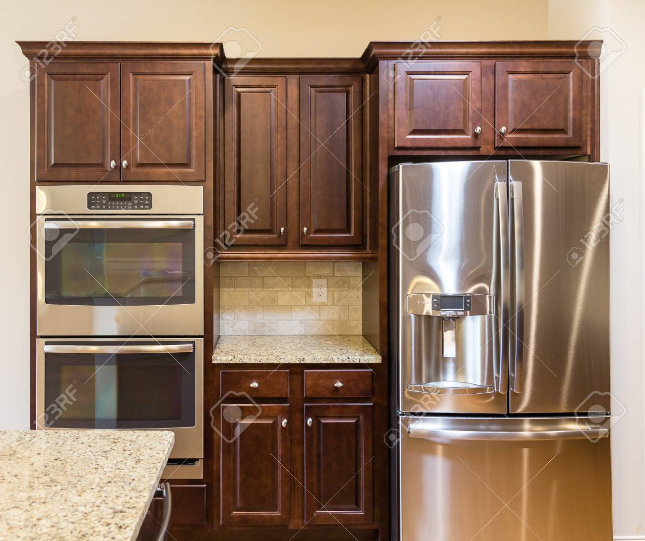 Stainless Steel Appliances, Granite Countertops And Dark Wood Cabinets In A  New Kitchen Stock Photo