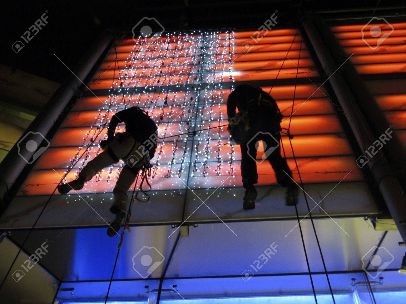 London, Oxford Street, June 2011: Workmen working overhead fixing lights at night. Stock Photo - 9890497