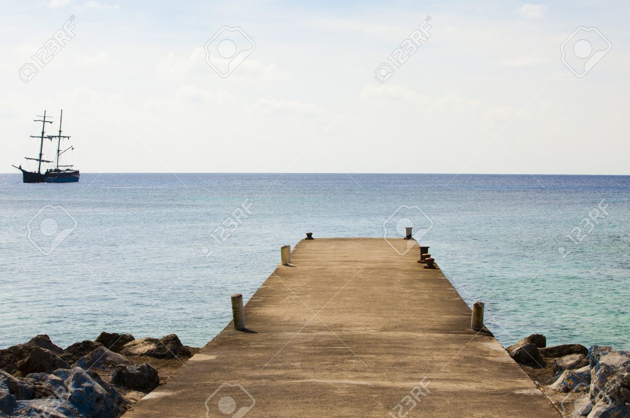 dock and pirate ship on the ocean stock photo picture and royalty