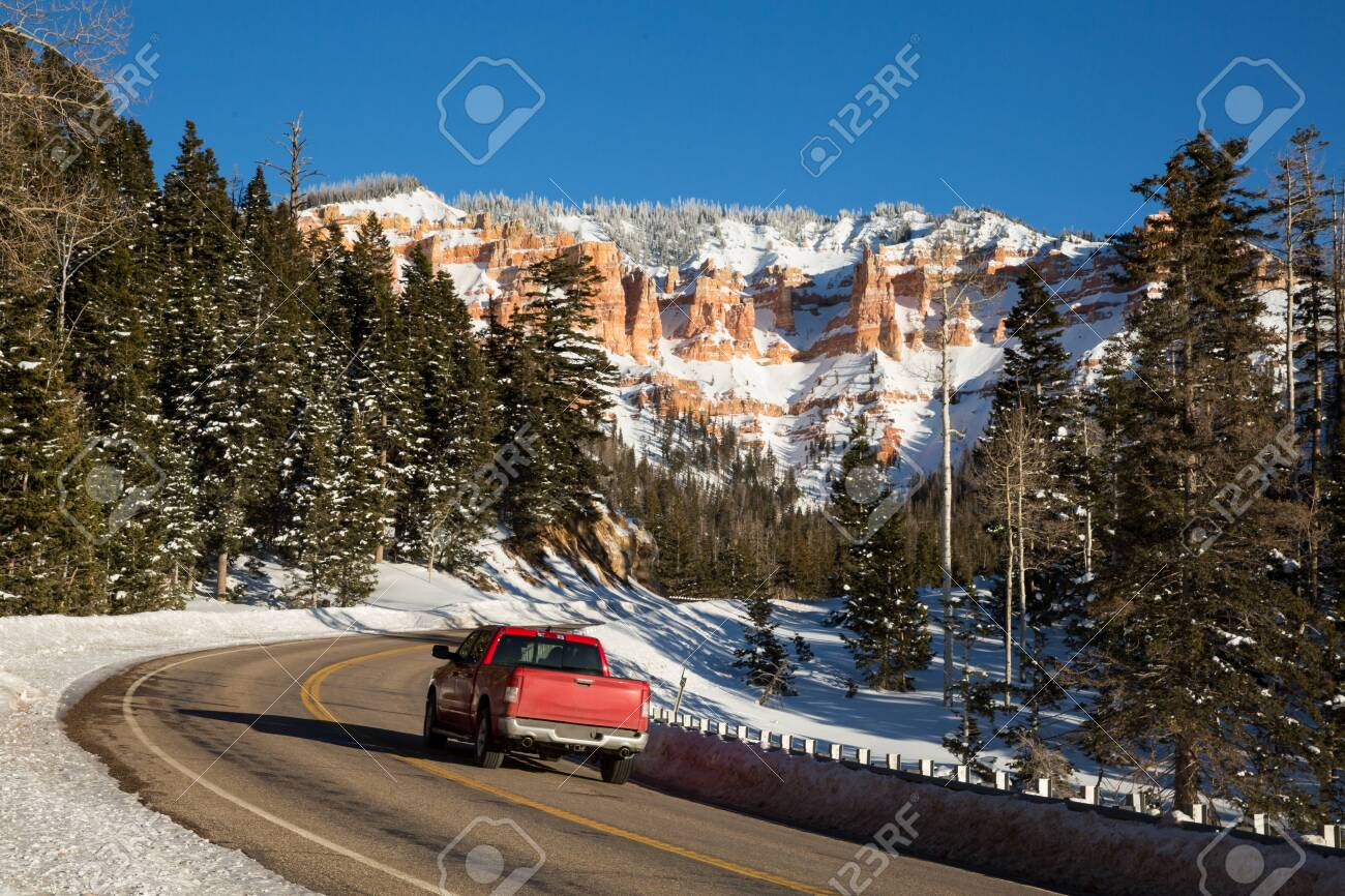 Red pickup driving up a winding canyon road toward snow covered rock formations in the red and orange sandstone. - 144644309