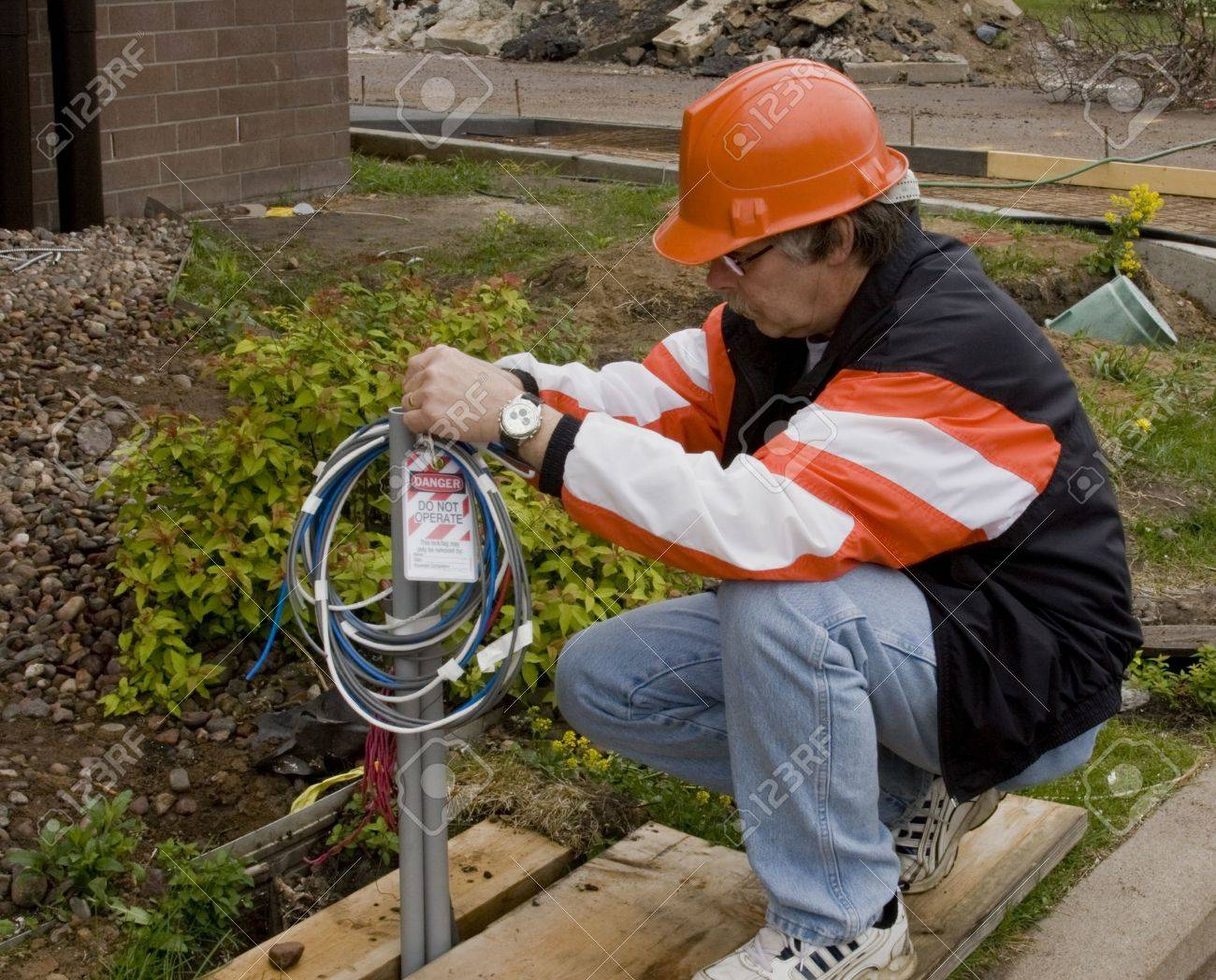 Construction Electrician Putting A Lockout Danger Tag On Wire