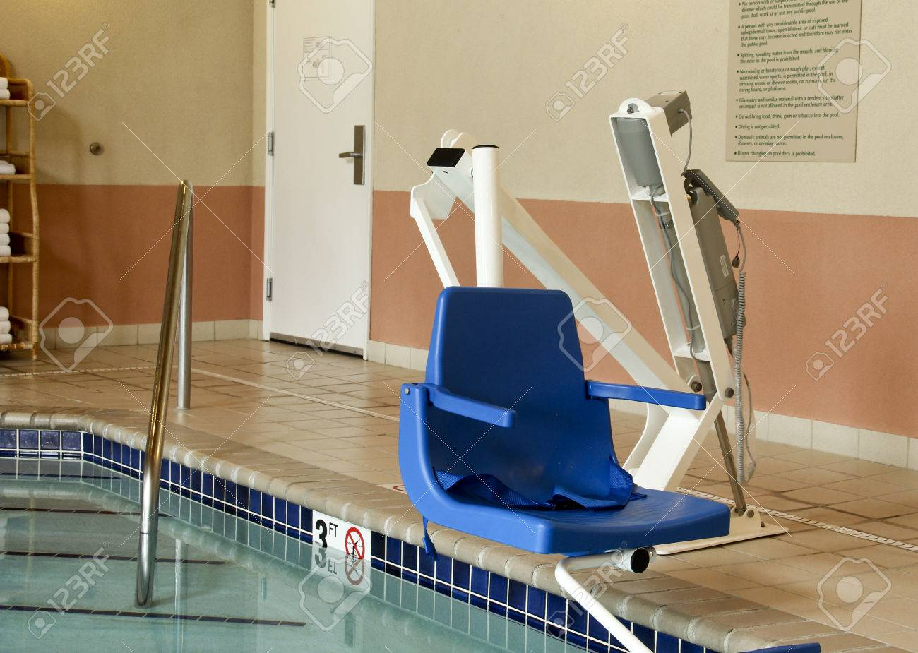 Stock Photo handicapped pool lift chair over an indoor pool  Handicapped  Pool Lift Chair Over. Lift Chair For Handicapped
