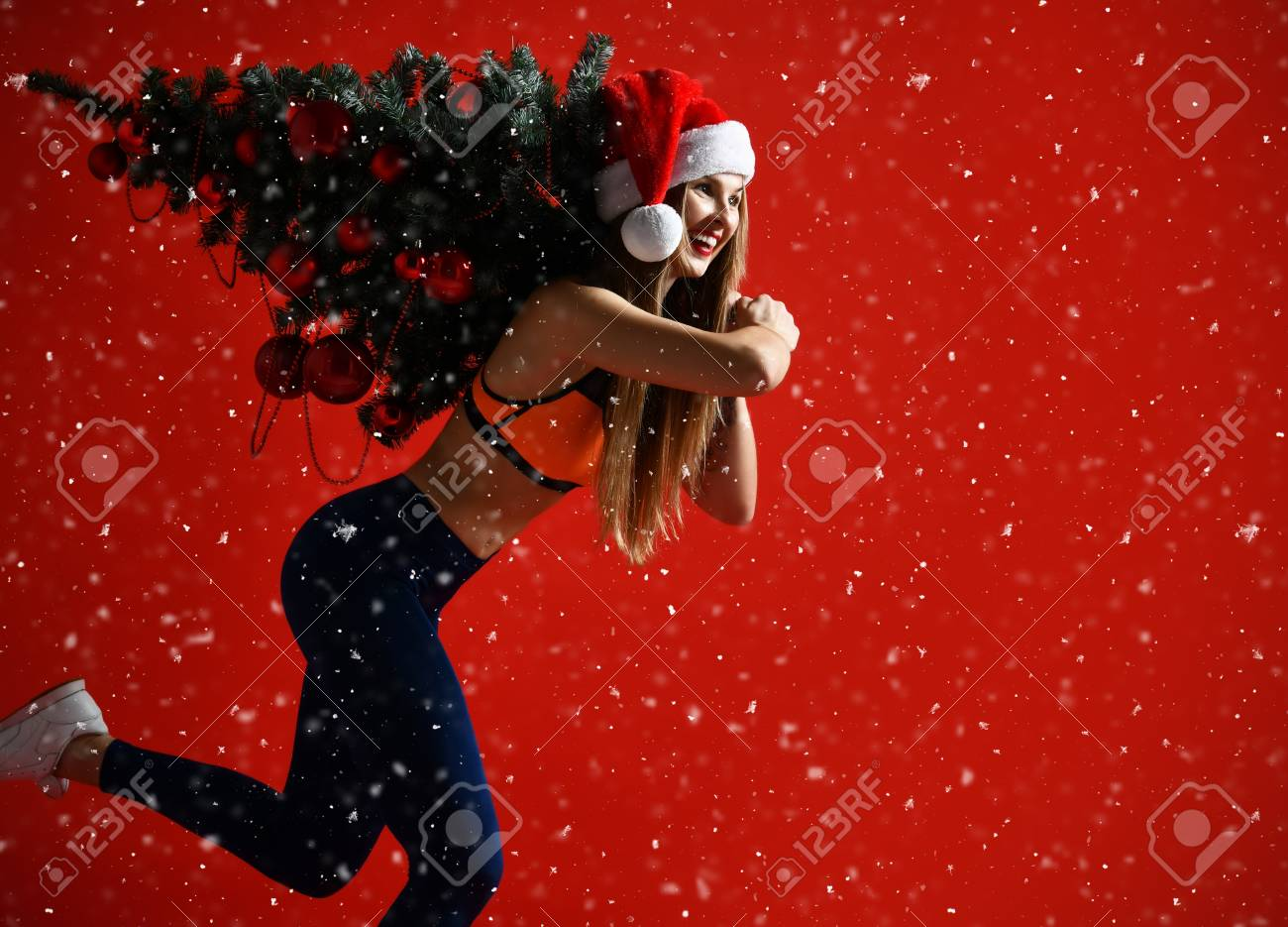 Christmas fitness sport woman wearing santa hat holding xmas tree on her shoulders. running forward on a snowing red background - 110768031