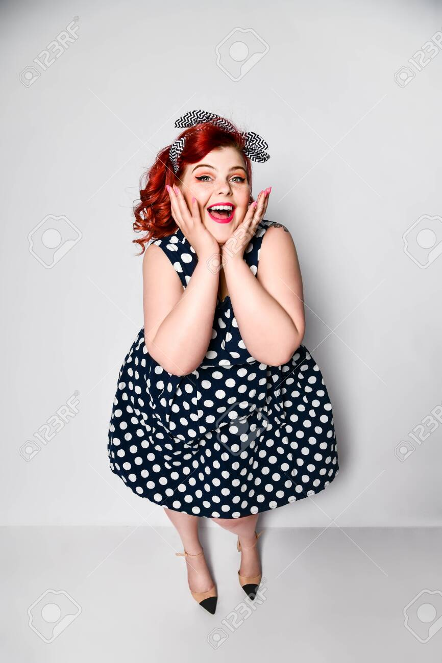 Cute portrait of a full-length red-haired woman plus size in..