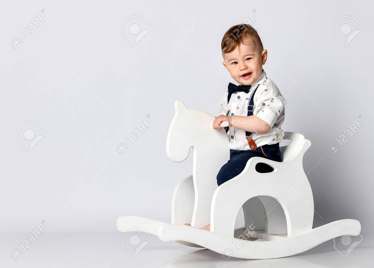 Funny Baby Sitting On The Toy Horse In White Studio Background Stock Photo Picture And Royalty Free Image Image 129165802