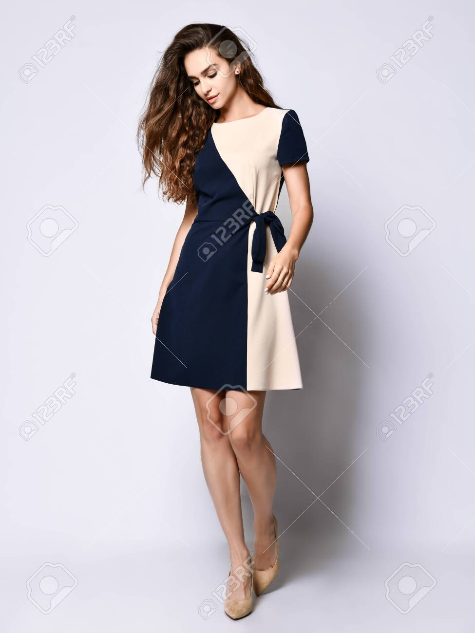 Luxurious curly female model in a two-tone dress and a full-length stilettos. Lovely girl in romantic clothes goes on a date, to the office, to a meeting. - 138157951