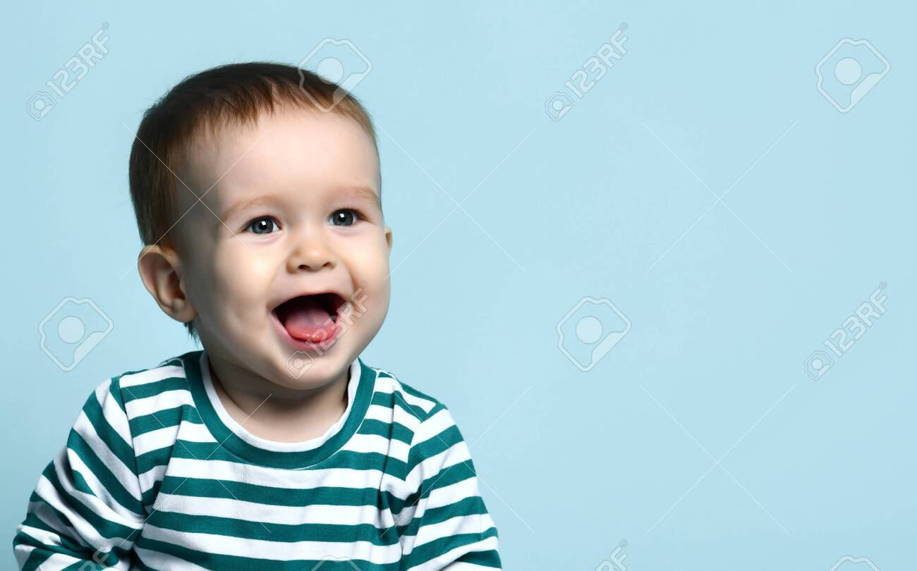 Portrait of a cute toddler 1 year old in a striped jacket on a blue background, rejoices laughing after seeing his mother - 138010544