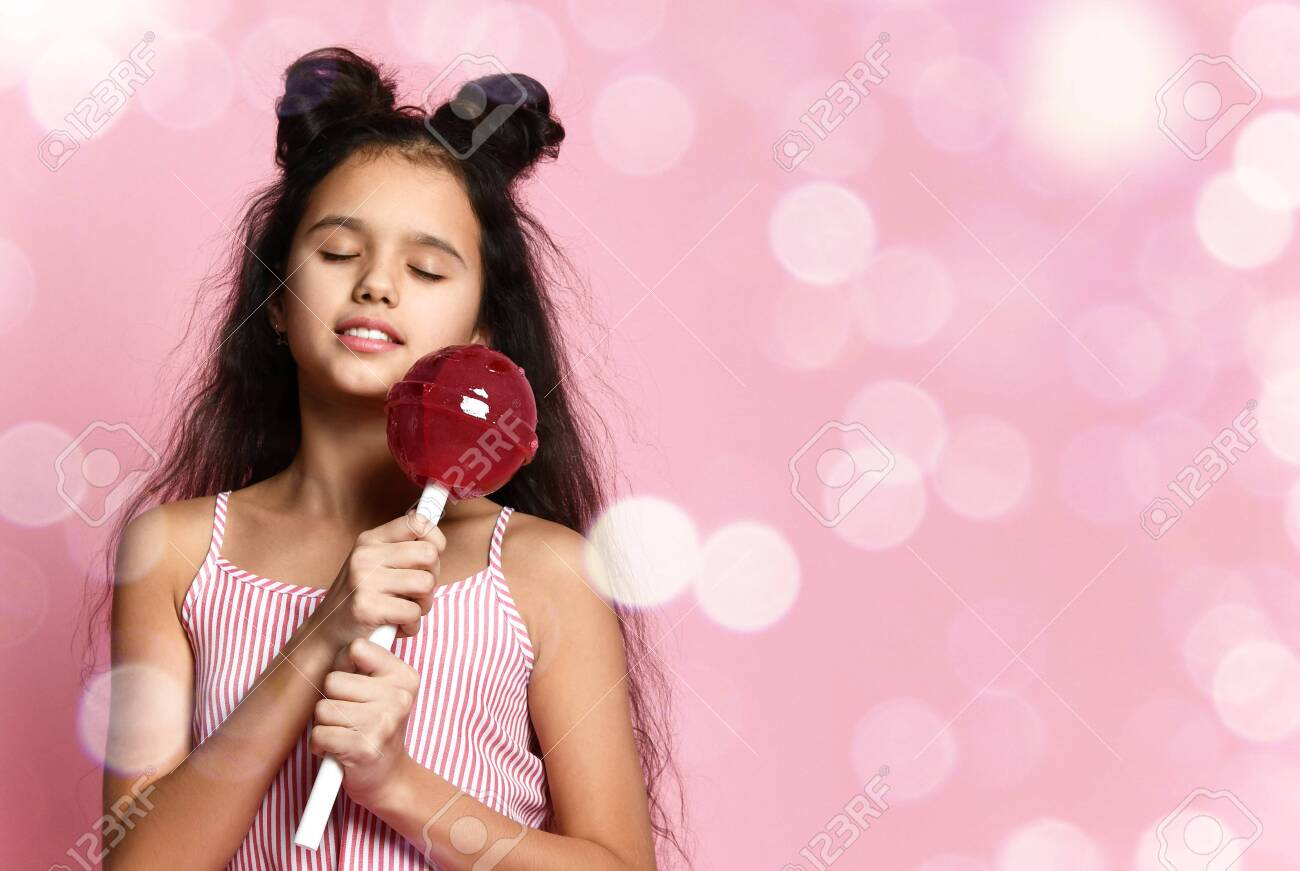 Brunette teenage girl with fancy hairstyle, in striped dress. She is smiling with closed eyes, holding a huge red lollipop while posing on pink studio background with bokeh. Fashion, beauty, sweets. Close up - 139364191