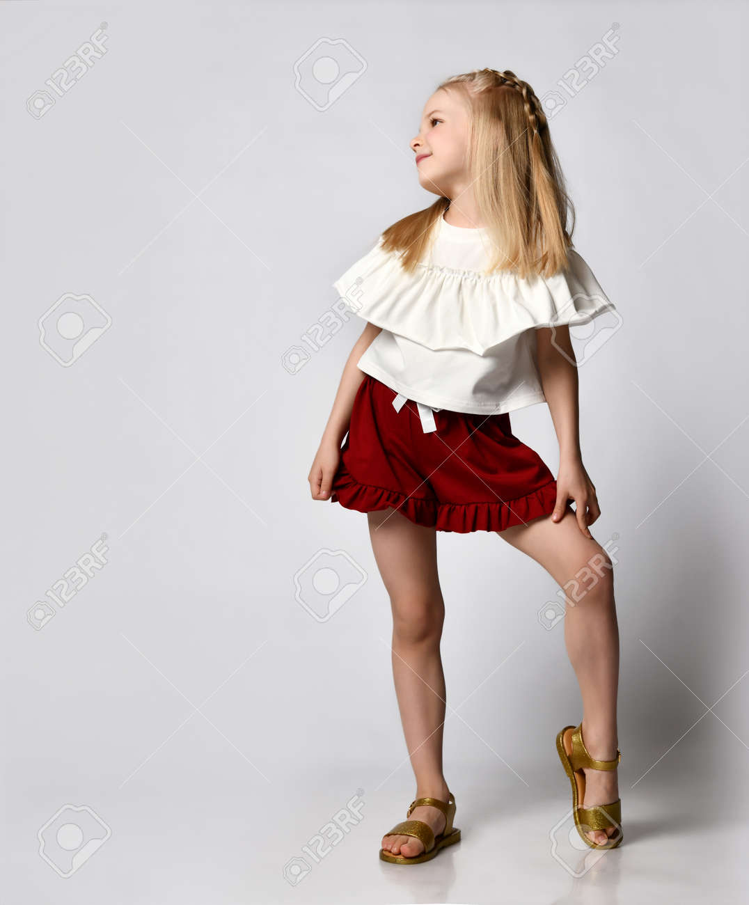 cute smiling little girl in a white blouse with ruffles, burgundy shorts and sandals, put her leg to the side - 169690048