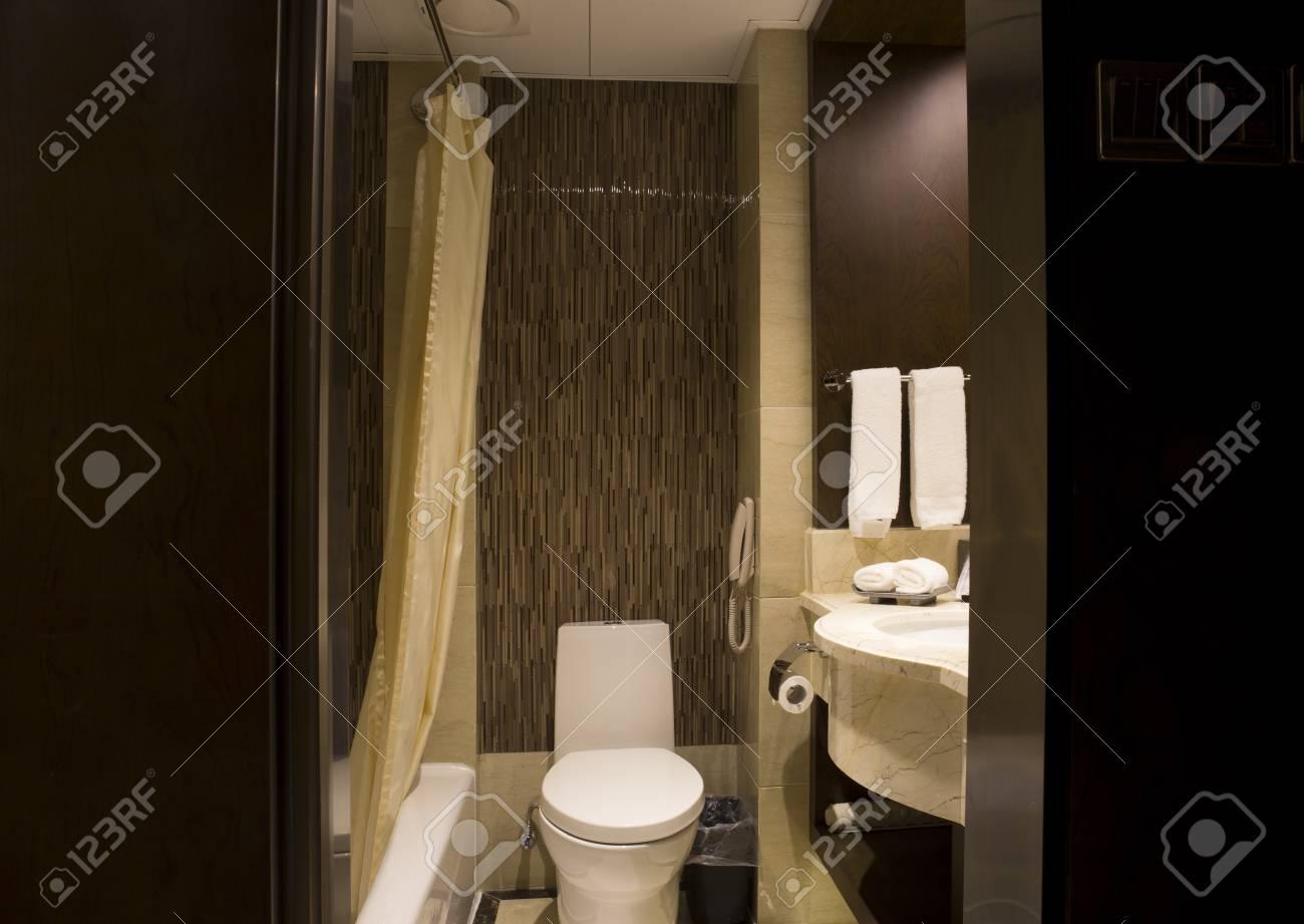 Aménagement de salle de bain moderne. Pommeaux de douche, grande baignoire,  grands miroirs sur les murs, lavabo en marbre noir.