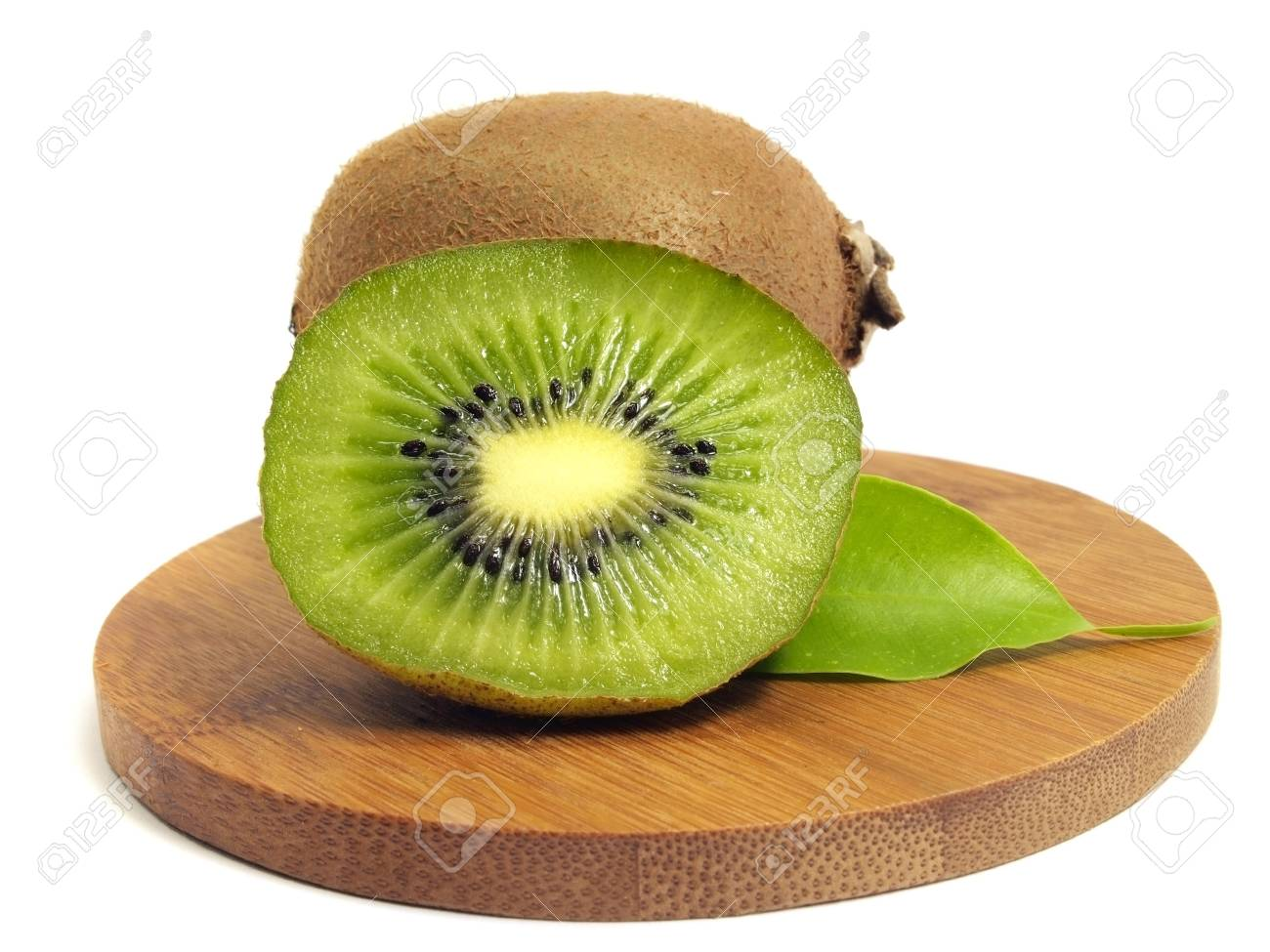 kiwi fruit wiht leaves on bamboo board on a white background Stock Photo - 12998645