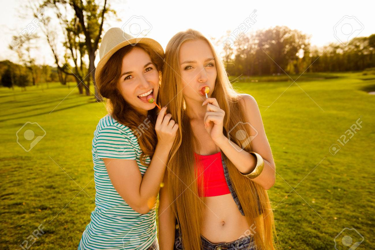 Two Playful Sexy Girls Licking Lollipops Stock Photo, Picture And ...