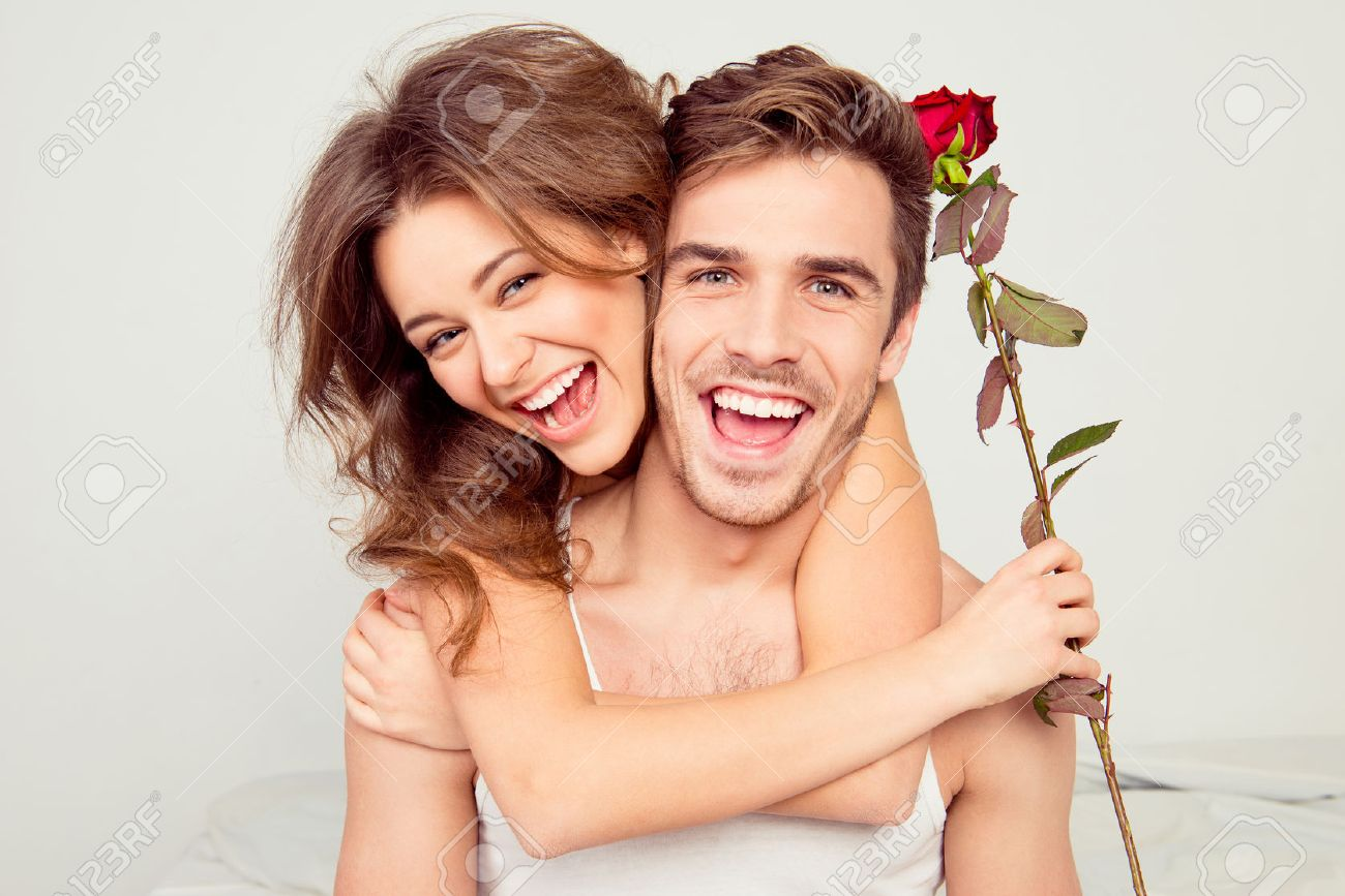 Cheerful young couple in love embracing in the bedroom with rose - 52410202