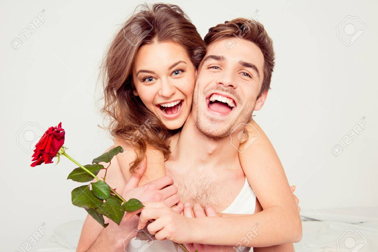 Cheerful young man and woman in love hugging in the bedroom with rose - 54648451