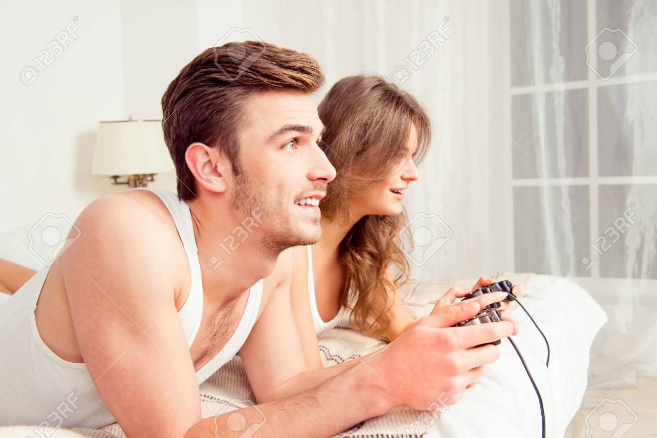 couple in love playing video games in bedroom side view stock