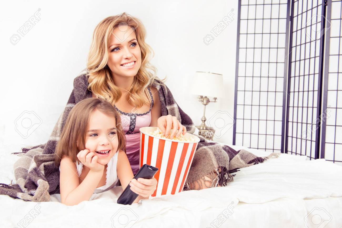 Excited mom and daughter watching tv and eating popcorn