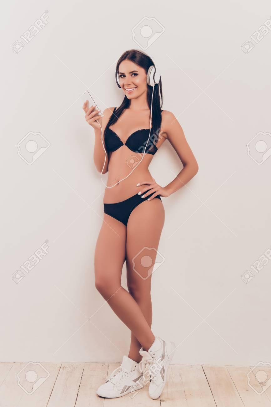 f85f6f76d Foto de archivo - Mujer bonita de escuchar música en los auriculares en ropa  interior negro