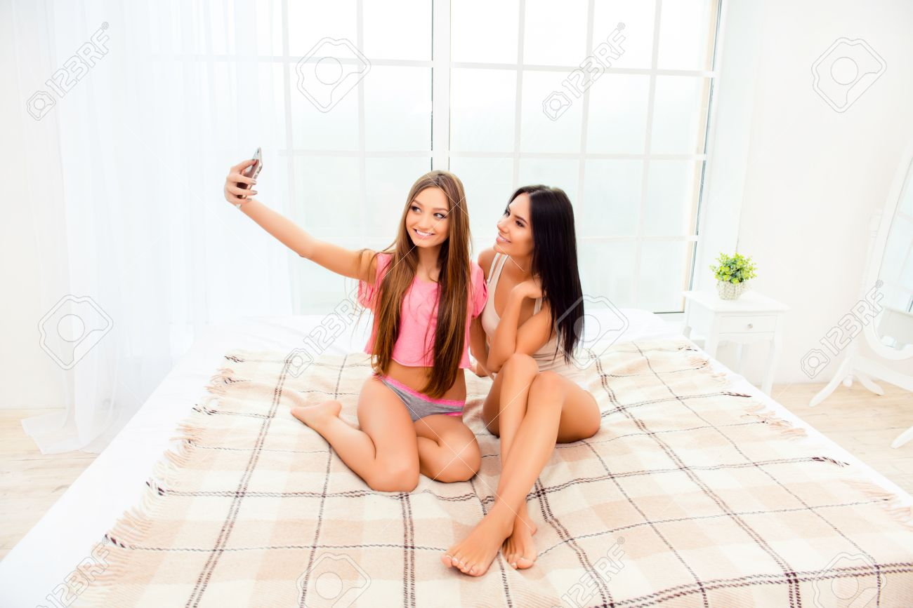 0070fddb1216 Sexy attractive girls in pajamas making selfie in bedroom Stock Photo -  61141005
