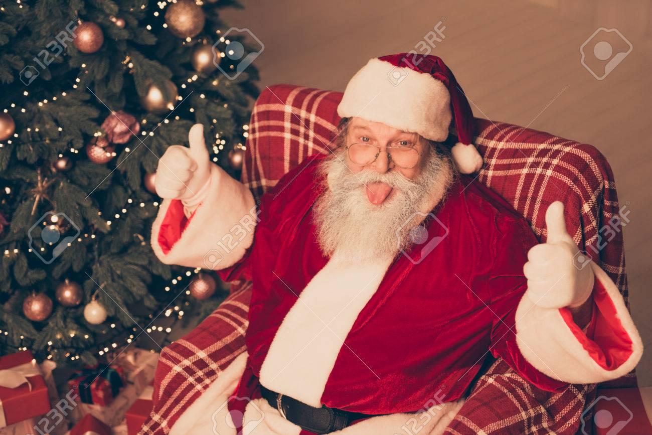 67192873 happy funny santa claus showing tongue and thumbs up - Free funny santa photos