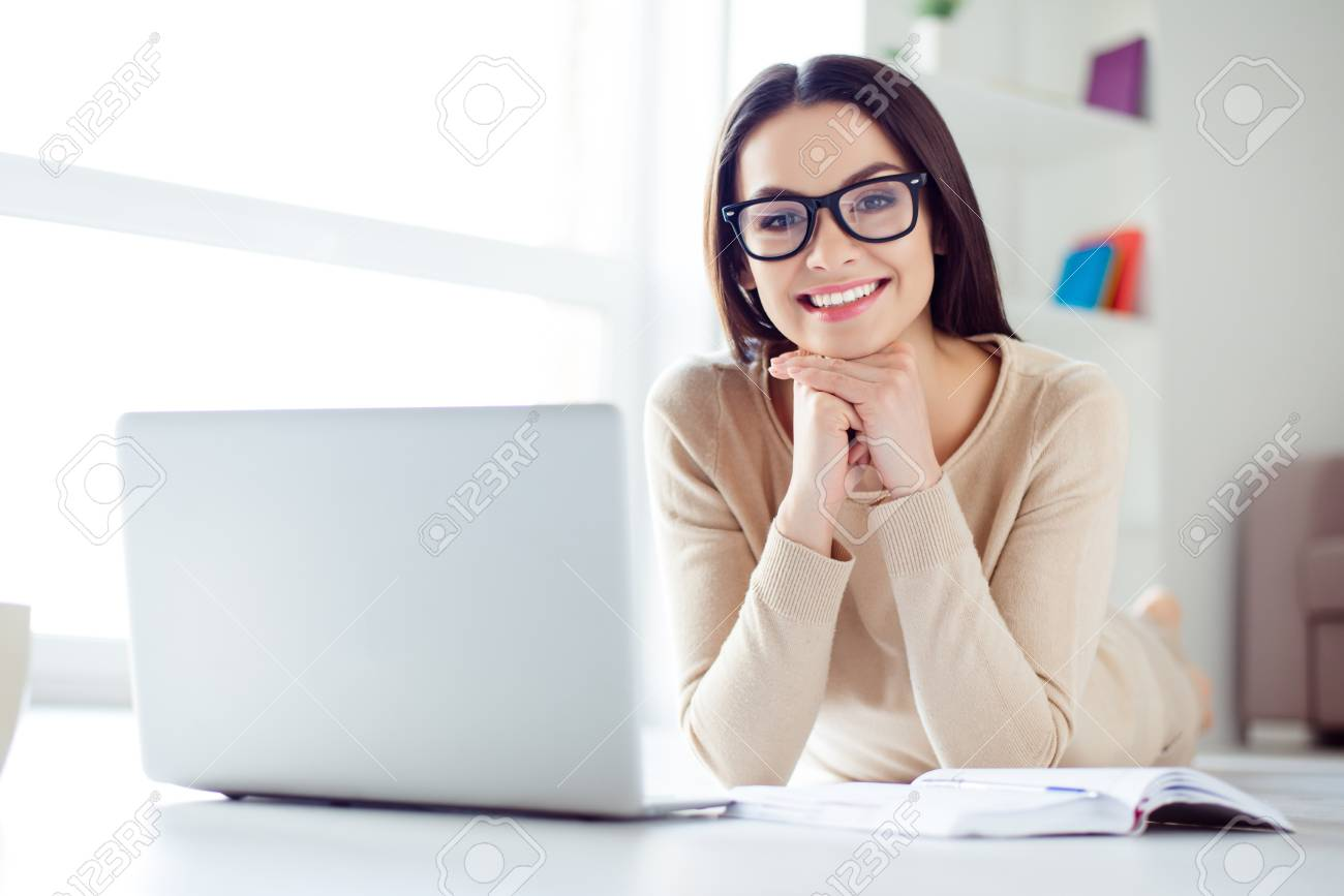 Portrait of cute nice-looking smiling businesswoman in glasses sitting at the table with laptop, notepad on it and holding up her head with hands - 80778610