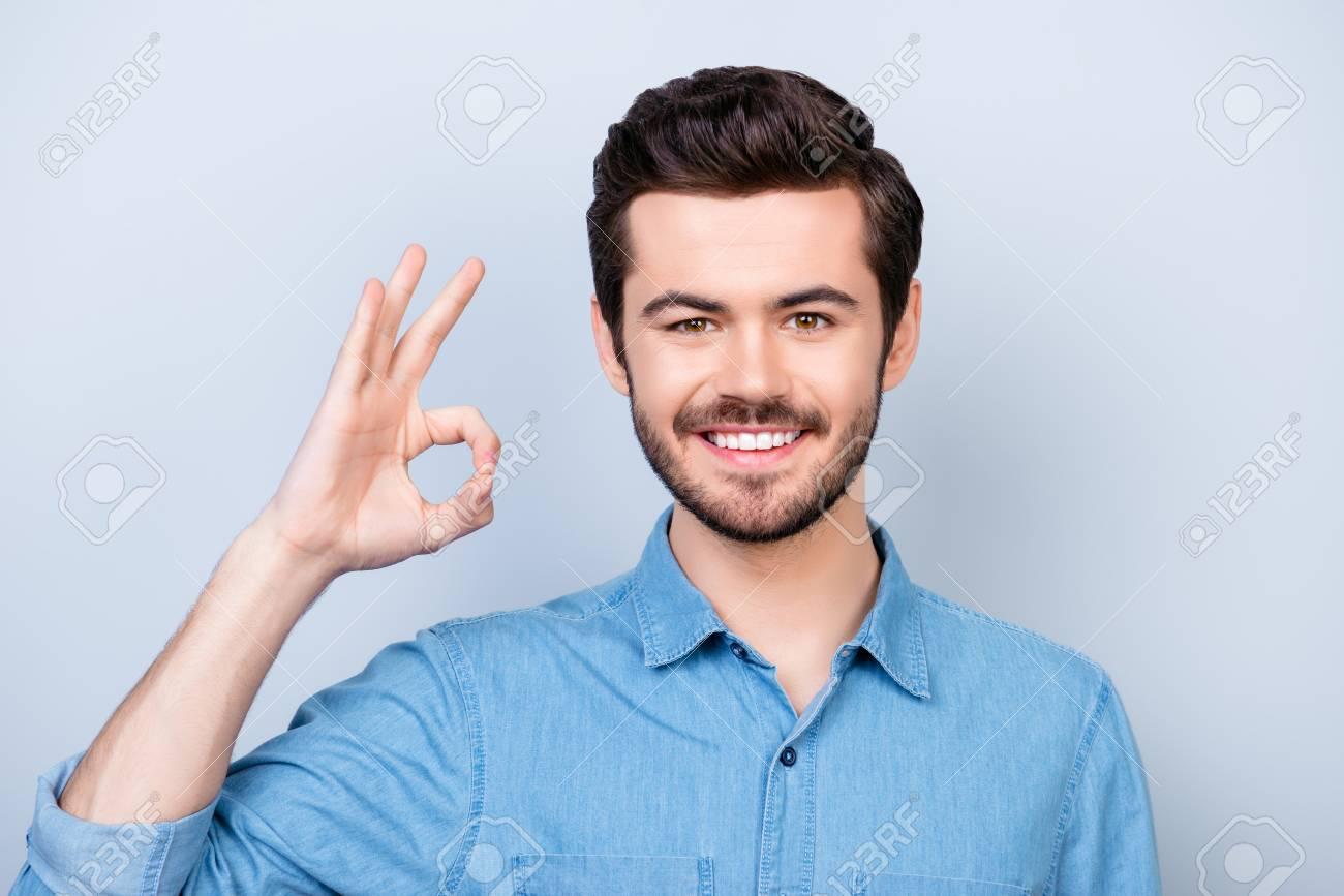 fd7b69a581 Il giovane uomo bello allegro in camicia dei jeans su priorità bassa  blu-chiaro sta mostrando il gesto